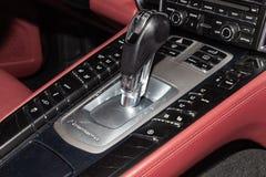 Närbild på kontrollbordet med en kugghjulväljare med ett stort antal knappar som klippas med rött läder i inre av a royaltyfria foton
