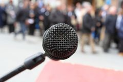Närbild på mikrofonen och det suddiga behind för folkmassa Fotografering för Bildbyråer