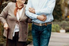 Närbild på personen som stöttar den höga kvinnan med den gå pinnen arkivfoton