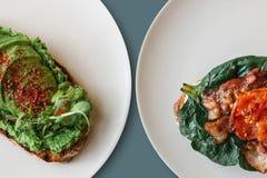 Närbild På plattorna är en smörgås med avokadot och bredvid den en smörgås eller ett rostat bröd med bacon och stekte tomater i a Royaltyfri Foto