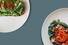 Närbild På plattorna är en smörgås med avokadot och bredvid den en smörgås eller ett rostat bröd med bacon och stekte tomater i a Royaltyfri Fotografi