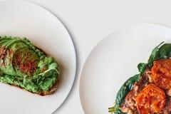 Närbild På plattorna är en smörgås med avokadot och bredvid den en smörgås eller ett rostat bröd med bacon och stekte tomater i a Arkivbilder