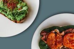 Närbild På plattorna är en smörgås med avokadot och bredvid den en smörgås eller ett rostat bröd med bacon och stekte tomater i a Royaltyfria Bilder