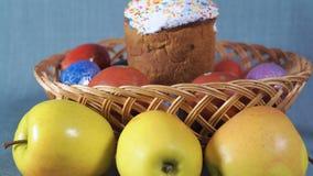 Närbild, påskordning, påsk i träkorgen med färgade ägg och Apple på bakgrunden stock video