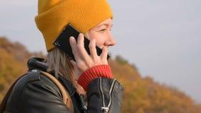 Närbild som en attraktiv Caucasian flicka i en gul hatt talar på hennes mobiltelefon utomhus i hösten le för flicka stock video