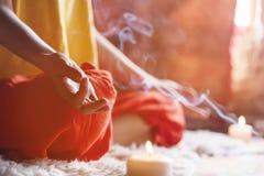 Närbild som en flicka som omges av stearinljus hemma på fönstret, mediterar i lotusblommapositionen som gör fingermudra bredvid arkivbild