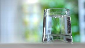 Närbild som häller renat nytt drinkvatten från flaskan på sommarbakgrund lager videofilmer