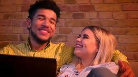 Närbild som skjutas av afrikansk grabb och caucasian flickan med bärbara datorn som kramar sig som är glad och hemma kopplas av lager videofilmer