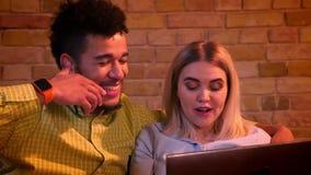 Närbild som skjutas av afrikansk grabb och caucasian flickan som sitter på soffan med bärbara datorn och joyfully hemma skrattar arkivfilmer