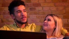 Närbild som skjutas av afrikansk grabb och caucasian flickan som sitter på soffan med bärbara datorn och lyckligt hemma talar med lager videofilmer