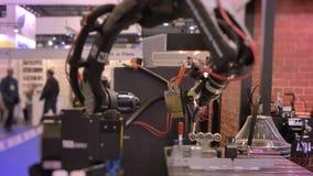 Närbild som skjutas av att flytta den svarta automatiska robotic armen för laser i process på utställningbakgrund stock video