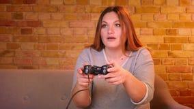 Närbild som skjutas av den fylliga hemmafrun som spelar videospelet genom att använda styrspaken som den är mycket uppmärksam och lager videofilmer