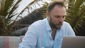 Närbild som skjutas av den lyckliga fokuserade Caucasian affärsmannen som använder bärbara datorn, direktanslutet tänker och arbe lager videofilmer