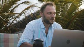 Närbild som skjutas av den lyckliga le Caucasian affärsmannen som använder bärbara datorn och att söka efter idéinspiration under stock video