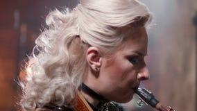 Närbild som skjutas av en kvinnlig musiker som utför på en saxofon lager videofilmer