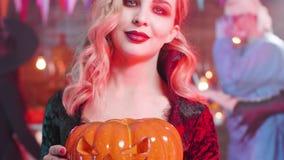 Närbild som skjutas av en ung sinnlig kvinna i dräkten av en vampyr på ett halloween parti stock video