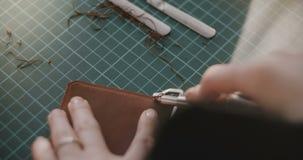 Närbild som skjutas av kvinnliga händer som arbetar, spjutspets av det lilla stycket av läder på en special tabell med det yrkesm arkivfilmer