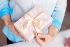 Närbild som skjutas av kvinnliga händer som rymmer en liten gåva slågen in med det rosa bandet Liten gåva i händerna av en kvinna royaltyfri foto
