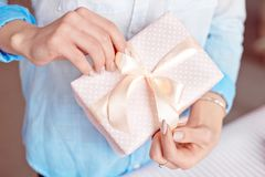 Närbild som skjutas av kvinnliga händer som rymmer en liten gåva slågen in med det rosa bandet Liten gåva i händerna av en kvinna royaltyfri bild