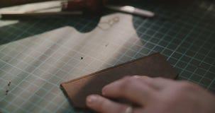 Närbild som skjutas av kvinnligt arbeta, spjutspetsen och som markerar för händer hål på stycke av läder med yrkesmässiga handhjä lager videofilmer