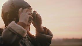Närbild som skjutas av liten lycklig pojke i för tappningflyg för gammal pilot- dräkt bärande exponeringsglas i solnedgångfältult stock video