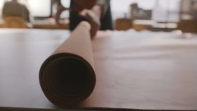 Närbild som skjutas av manliga hantverkarehänder som fördelar ett stort rullstycke av läder på den stora ljusa fabriks- seminariu arkivfilmer