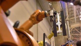 Närbild som skjutas av olika rörande automatiska robotic armar i process på utställningbakgrund stock video
