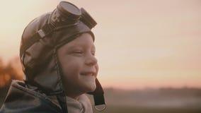 Närbild som skjutas av rolig pys i gammal pilot- dräkt med halsduken och exponeringsglas som gör enfaldiga framsidor i en fältult stock video