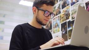 Närbild som skjutas av ung stilfull affärsman i exponeringsglas och att skriva på hans smartphone och bärbar dator, mot kontorsba arkivfilmer