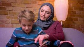 Närbild som uppmärksamt hemma skjutas av koncentrerad liten pojke och hans muslim moder i hijabläsebok arkivfilmer