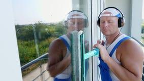 Närbild stående av en manlig arbetare av lokalvårdservice, i blåa overaller, med hörlurar, och att göra ren, tvättande Windows arkivfilmer
