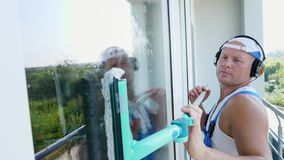 Närbild stående av en manlig arbetare av lokalvårdservice, i blåa overaller, med hörlurar, och att göra ren, tvättande Windows stock video