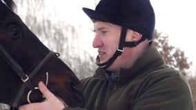 Närbild, stående av en manlig ryttare och framsidan av en härlig svart häst Snöig vinterdag utomhus lager videofilmer