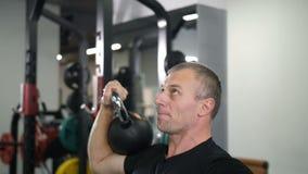 Närbild Stilig grabb som gör övning med en kettlebell i idrottshallen 4K långsam Mo lager videofilmer