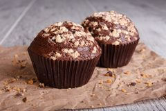 Närbild två chokladmuffin med muttrar på en tabellbakgrund Chokladmuffin hemlagad bakelse arkivbild