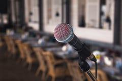 Närbildavtryck av en röd läppstiftsångare på en silverjärnmikrofon på stirrandena på etappen Levande musik för begrepp i a royaltyfri bild
