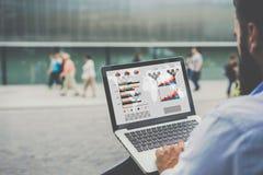 Närbildbärbar dator med grafer, diagram och diagram på skärmen i händer av affärsmansammanträde utomhus och att arbeta royaltyfria bilder