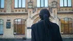 Närbildbaksida-sikt av den unga afrikansk amerikanstudenten med dreadlocks som går till universitetet i solsken arkivfilmer