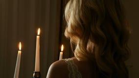 Närbildbaksidasikt av blondinen med lockigt hår som rymmer kandelaber med blixtstearinljus i det mörka rummet arkivfilmer
