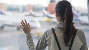 Närbildbaksikt av flickan med ryggsäcken som ut ser fönstret på flygplatsen på flygplanbakgrund stock video