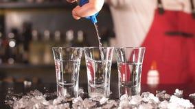Närbildbartender som häller någon drink från flaskan in i sköt exponeringsglas på träräknare arkivfilmer