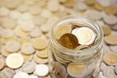 Närbildbild av en exponeringsglaskrus mycket av nya mynt för thailändsk baht royaltyfri bild
