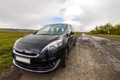 Närbildbild av en modern bil på en dålig väg Arkivbild