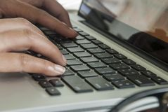 Närbildbild av en ung kvinna som skriver på en bärbar dator royaltyfria bilder