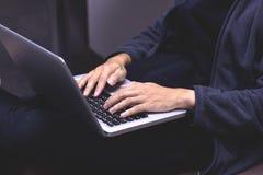 Närbildbild av en ung man som hemma arbetar på hans bärbar dator han arkivfoto