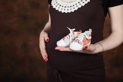 Närbildbild av gravida kvinnan som trycker på hennes buk med händer Arkivfoton