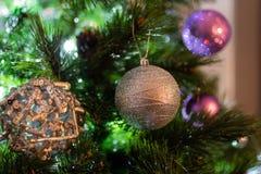 Närbildbild med silver- och purpplejulbollar på träd arkivfoto