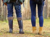 Närbildbilden av ben av ett par som går i skog, campar, turnerar Royaltyfria Bilder