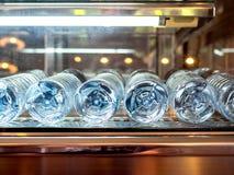 Närbildbottensikt av mineraliska nya dricksvattenflaskor i kylskåp arkivfoto