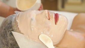 Närbildcosmetologisten applicerar en tjock beige maskering på framsidan och ögonen av kvinnan stock video